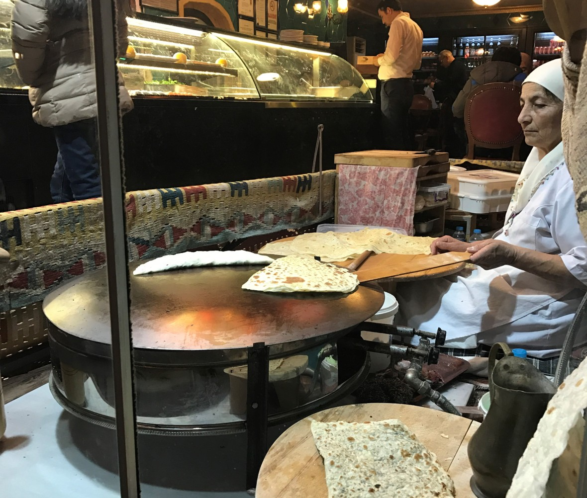 woman-making-fresh-flatbread-by-the-restaurant-window-istanbul-turkey